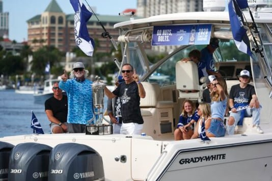 Tampa Bay Lightning coach Jon Cooper, right, steadies the Prince of Wales trophy as his boat is launched for the NHL hockey Stanley Cup champions' boat parade, Wednesday, Sept. 30, 2020, in Tampa, Fla. (Dirk Shadd/Tampa Bay Times via AP)