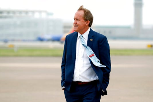 FILE - In this June 28, 2020 file photo, Texas State's Attorney General Ken Paxton waits on the flight line for the arrival of Vice President Mike Pence at Love Field in Dallas. The lawyer Texas Attorney General Ken Paxton hired to investigate a political donor's claims of wrongdoing by the FBI has no prosecutorial experience and ties to the donors defense attorney.  Paxtons hiring of an
