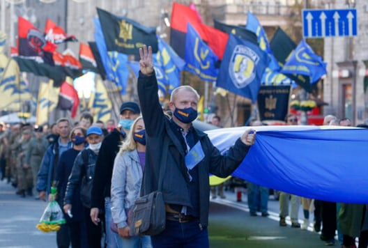 People carry the Ukrainian National flag at a rally marking Defender of Ukraine Day in centre Kyiv, Ukraine, Wednesday, Oct. 14, 2020. (AP Photo/Efrem Lukatsky)