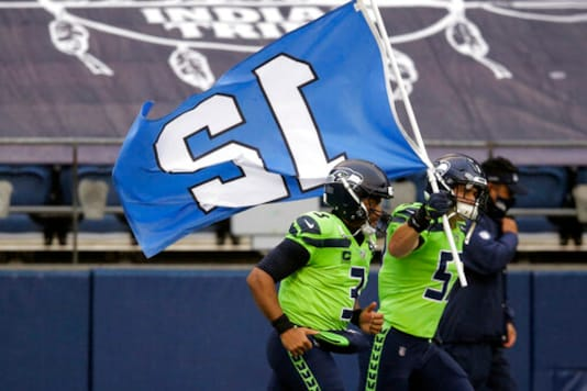 Seattle Seahawks' Cody Barton carries the 12th flag onto the field as he runs with quarterback Russell Wilson before an NFL football game against the Minnesota Vikings, Sunday, Oct. 11, 2020, in Seattle. (AP Photo/John Froschauer)