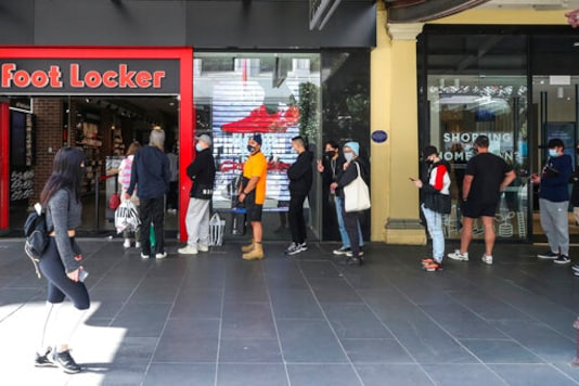 Customers line up outside a sportswear retailer in Melbourne, Australia, Wednesday, Oct. 28, 2020. Australias second largest city of Melbourne which was a coronavirus hotspot emerges from a nearly four-months lockdown, with restaurants, cafes and bars opening and outdoor contact sports resuming on Wednesday. (AP Photo/Asanka Brendon Ratnayake)