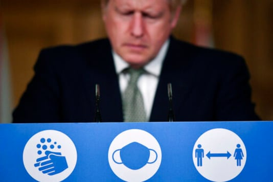 Britain's Prime Minister Boris Johnson listens during a coronavirus briefing in Downing Street, London, Monday, Oct. 12, 2020. (Toby Melville/Pool Photo via AP)