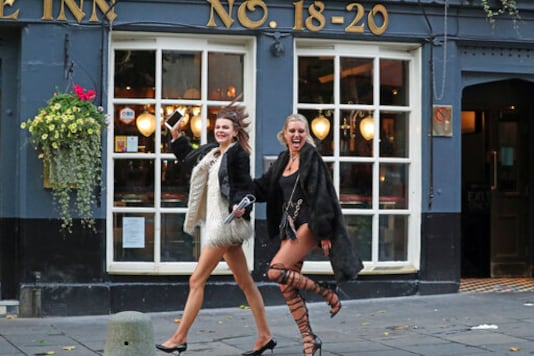 Two women walk past pubs in Edinburgh, as temporary restrictions announced by First Minister Nicola Sturgeon to help curb the spread of coronavirus have come into effect from 6pm, in Edinburgh, Friday, Oct. 9, 2020. (Andrew Milligan/PA via AP)
