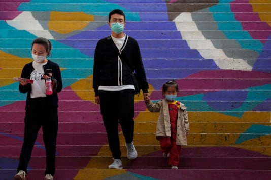 A family wearing face masks to help curb the spread of the coronavirus walk down a colourful staircase at a shopping mall in Beijing, Sunday, Oct. 11, 2020. Even though the spread of COVID-19 has been all but eradicated in China, the pandemic is still surging across the globe with ever rising death toll. (AP Photo/Andy Wong)