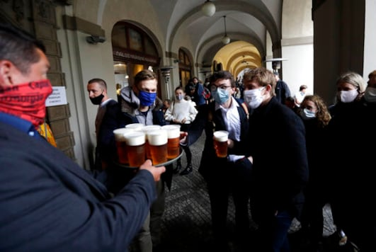 FILE - In this file photo people line up for a beer at a restaurant terrace in Prague, Czech Republic, Monday, May 11, 2020. (AP Photo/Petr David Josek, File)