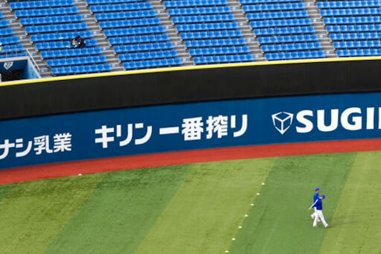 A stadium crew member, upper left, installs a device to detect carbon dioxide in the seats of a baseball stadium, home for the Yokohama DeNA BayStars, in Yokohama, south of Tokyo on Friday, Oct. 30, 2020. The device was introduced during a media tour before a Japanese professional baseball league game between the Hanshin Tigers and the DeNA BayStars on Friday. (AP Photo/Hiro Komae)