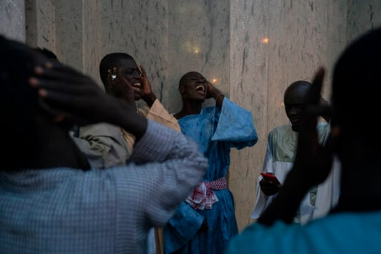 Pilgrims from the Mouride Brotherhood sing poems written by Cheikh Amadou Bamba outside the Grand Mosque of Touba as they take part in the celebrations of the Grand Magal of Touba, Senegal, Monday, Oct. 5, 2020. Despite the coronavirus pandemic, thousands of people from the Mouride Brotherhood, an order of Sufi Islam, are gathering for the annual religious pilgrimage to celebrate the life and teachings of Cheikh Amadou Bamba, the founder of the brotherhood. (AP Photo/Leo Correa)