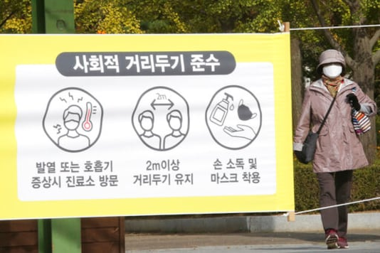 A woman wearing a face mask to help protect against the spread of the coronavirus walks by a social distancing sign at a park in Goyang, South Korea, Thursday, Oct. 15, 2020. South Korea reported more than 100 new cases of the coronavirus, half of them linked to a hospital in Busan. The signs read: