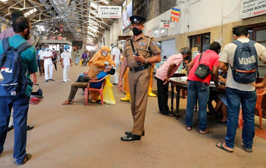 A Sri Lankan police officer stands guard as health officers collect swab samples from rail commuters to test for COVID-19 at a railway station in Colombo, Sri Lanka, Monday, Oct. 12, 2020. (AP Photo/Eranga Jayawardena)