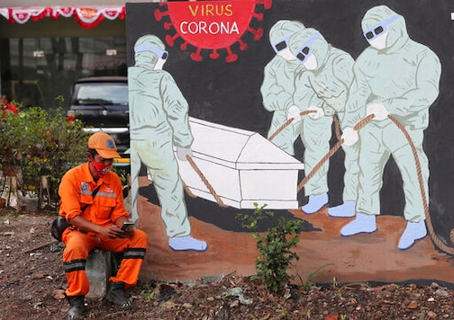 FILE - In this Aug. 14, 2020, file photo, a street sweeper checks his mobile phone as he takes a break near a coronavirus-themed mural in Jakarta, Indonesia. The World Bank has approved $12 billion in financing to help developing countries buy and distribute coronavirus vaccines, tests, and treatments, aiming to support the vaccination of up to 1 billion people, the bank said in a statement late Tuesday, Oct. 13, 2020. (AP Photo/Tatan Syuflana, File)