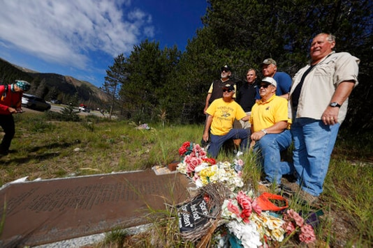 membrs of the 1970 Wichita State University Shockers football team stand around a plaque for their teammates who died in an airplane crash as the survivors visit the crash site near Loveland Pass Monday, July 27, 2020, west of Silver Plume, Colo. Wreckage from the plane, which was one of two being used to take the Shockers to play a football game against Utah State University in Logan, Utah, is still scattered on the mountain top nearly 50 years after the crash close to the Eisenhower Tunnel. (AP Photo/David Zalubowski)