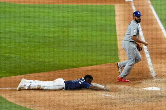 Tampa Bay Rays' Randy Arozarena, left, scores the winning run past Los Angeles Dodgers relief pitcher Kenley Jansen in Game 4 of the baseball World Series Saturday, Oct. 24, 2020, in Arlington, Texas. Rays defeated the Dodgers 8-7 to tie the series 2-2 games. (AP Photo/Eric Gay)