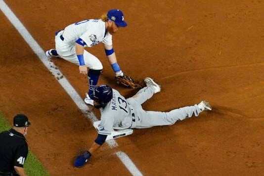 Tampa Bay Rays' Manuel Margot is safe at third past Los Angeles Dodgers third baseman Justin Turner on a ball hit by Joey Wendle during the second inning in Game 2 of the baseball World Series Wednesday, Oct. 21, 2020, in Arlington, Texas. (AP Photo/David J. Phillip)