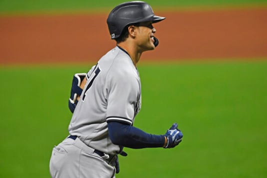 New York Yankees' Giancarlo Stanton (27) runs the bases after hitting a solo home run off Cleveland Indians relief pitcher Cam Hill (27) in the ninth inning of Game 1 of an American League wild-card baseball series, Tuesday, Sept. 29, 2020, in Cleveland. The Yankees won 12-3. (AP Photo/David Dermer)