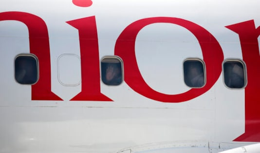 Yemeni prisoners peer through windows of a plane during their arrival after being released by the Saudi-led coalition at the airport in Sanaa, Yemen, Thursday, Oct. 15, 2020. (AP Photo/Hani Mohammed)