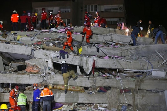 Members of rescue services search in the debris of a collapsed building for survivors in Izmir, Turkey, early Saturday. A strong earthquake struck Friday in the Aegean Sea between the Turkish coast and the Greek island of Samos, killing several people and injuring hundreds amid collapsed buildings and flooding. (AP Photo/Emrah Gurel)