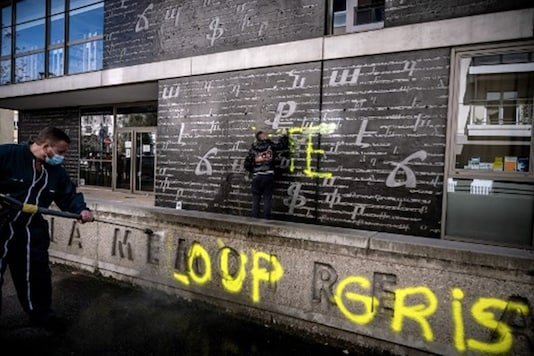 Men clean an outside wall of the National Armenian Memorial Centre in Decines-Charpieu, near Lyon, on November 1, 2020 where pro-Turkish yellow letters graffiti tags have been painted overnight. (Photo by JEFF PACHOUD / AFP)
