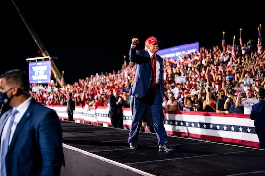 """A group of people wave flags in support of President Donald Trump's re-election, in Laconia, N.H., on Monday, Nov. 2, 2020. If Trump pieces together an Electoral College win on Tuesday, at least one pollster — and perhaps only one — will be able to say, """"I told you so."""" (Hilary Swift/The New York Times) President Donald Trump raises a fist during a campaign rally at Miami-Opa locka Executive Airport in Opa-locka, Fla., Nov, 1, 2020. If Trump pieces together an Electoral College win on Tuesday, at least one pollster — and perhaps only one — will be able to say, """"I told you so."""" (Doug Mills/The New York Times)"""