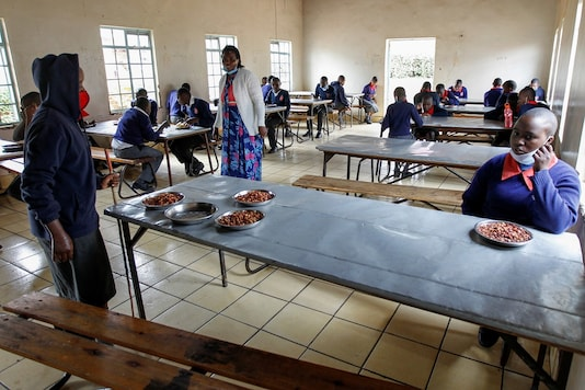 Visually impaired pupils practice social distancing while the headteacher Margaret Njuguna guides them during lunch at the Thika school for the blind in Thika town of Kiambu county, Kenya. (REUTERS/Monicah Mwangi)