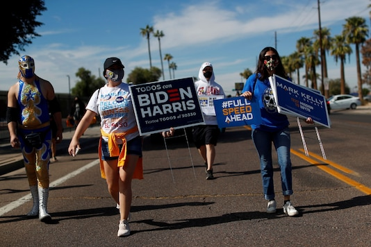 FILE PHOTO: People carry posters in support of Democratic U.S. presidential nominee Joe Biden, vice presidential candidate Kamala Harris, and senate candidate Mark Kelly, during an event to promote the importance of the Latino vote, in the majority Hispanic neighbourhood of Maryvale in Phoenix, Arizona U.S., October 31, 2020. REUTERS/Edgard Garrido/File Photo