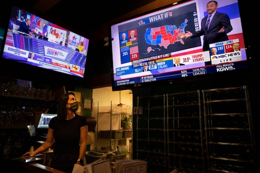 A bartender watches election results on television at a bar and grill Tuesday, Nov. 3, 2020, in Portland, Ore. (AP Photo/Paula Bronstein)