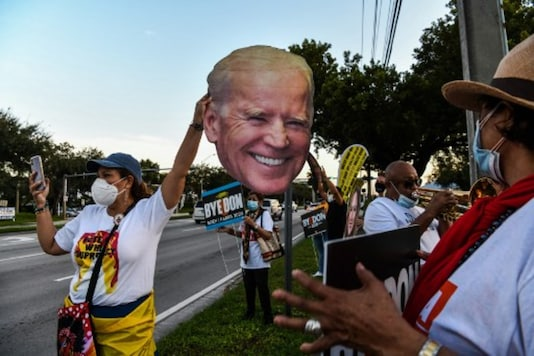 Supporters of the Democratic party hold signs and a Joe Biden mask outside the Miami-Dade County Election Department in Miami, Florida, on November 3. (AFP)