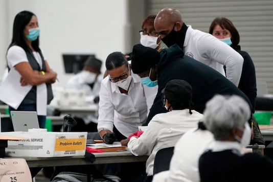 Election officials huddle around a table as absentee ballots are processed at the central counting board, Wednesday, Nov. 4, 2020, in Detroit. (AP Photo/Carlos Osorio)