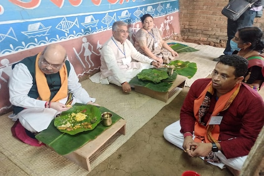 Home Minister Amit Shah lunches at a tribal family's residence in Bankura along with Bengal BJP leader Dilip Ghosh and other party functionaries on Thursday. (News18)