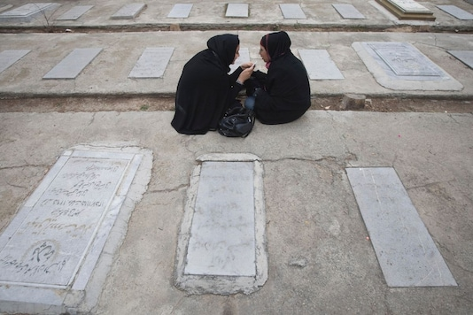 Two schoolgirls sit next to the graves of Iranians who were killed during Iran's Islamic revolution (1979) during a ceremony at the Behesht-e Zahra (Zahra's paradise) cemetery in southern Tehran February 1, 2010. REUTERS/Morteza Nikoubazl