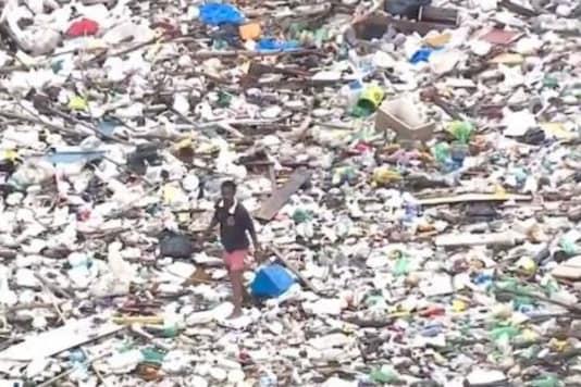 Video grab of man walking on garbage-filled river. (Credit: Facebook/ @Edson Passos News)
