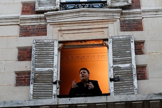 FILE PHOTO: French tenor singer Stephane Senechal sings from his apartment window in Paris as a lockdown is imposed for Covid-19. REUTERS/Gonzalo Fuentes/File Photo