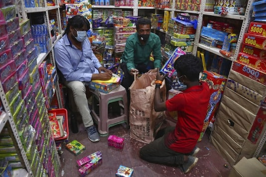People wearing face masks as a precaution against the coronavirus sell firecrackers ahead of Diwali, the festival of lights, in Hyderabad. (AP Photo)