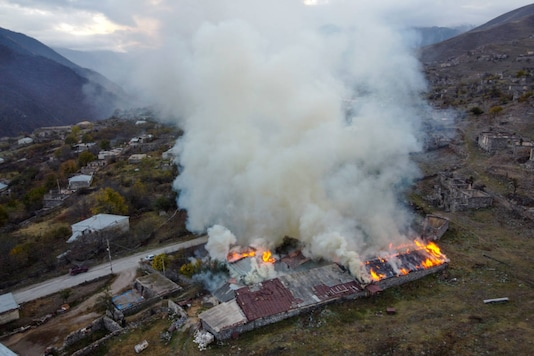 Smoke rises from a burning house in an area once occupied by Armenian forces but soon to be turned over to Azerbaijan, in Karvachar, the separatist region of Nagorno-Karabakh, on November 13, 2020. (AP Photo/Dmitry Lovetsky)