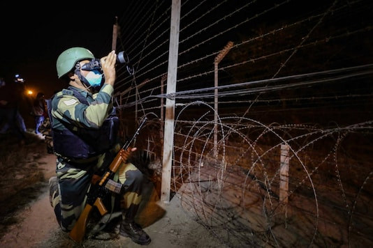 A Border Security Force (BSF) personnel patrols near India-Pakistan international border, on the outskirts of Jammu.(PTI Photo)