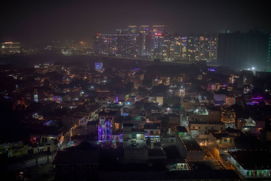 A layer of smog envelops the skyline as residential buildings are decorated with colourful lights during Diwali, on the outskirts of New Delhi, on November 14, 2020. (AP Photo/Altaf Qadri)