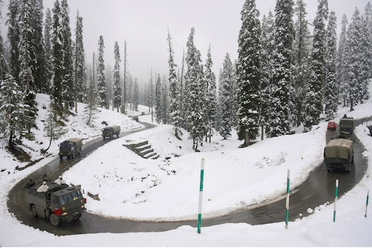 An army convoy moves on a snow covered road after the season's first snowfall, at Gulmarg in Baramulla district of north Kashmir, Monday, Nov. 16, 2020. (PTI Photo/S. Irfan)