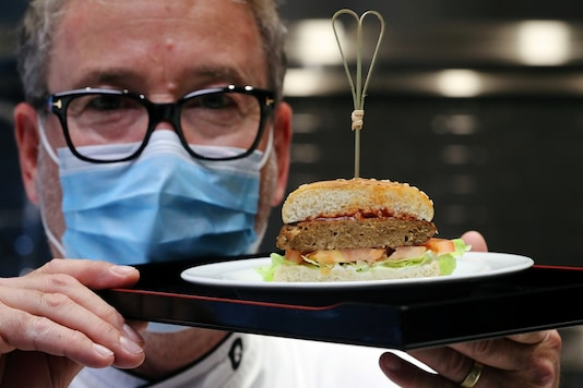 Chef Sam Brunschweiler wears a protective mask as he displays a pea protein-based hamburger with vegan juicy meat flavor, tomato, salad and sesame bun. (REUTERS/Arnd Wiegmann