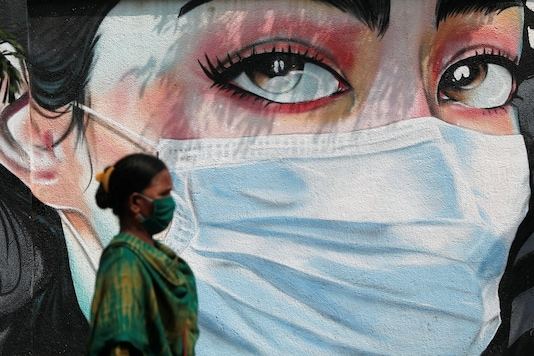 A woman walks past a graffiti of a girl wearing a protective mask. (Image for representation)