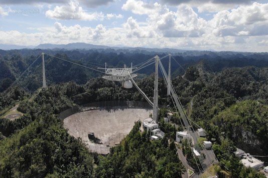 The Arecibo Observatory space telescope, which was damaged in August and in November from broken cables which tore holes in the structure, is seen in Arecibo, Puerto Rico. (Credit: UCF/Handout via REUTERS)