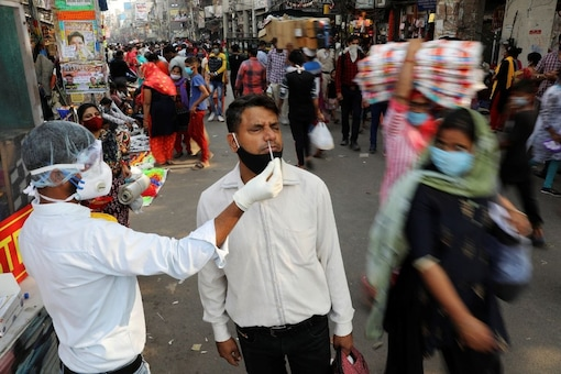 A healthcare worker collects a swab sample from a man amidst the spread of the coronavirus disease (COVID-19), at a market, in the old quarters of Delhi. (Reuters)