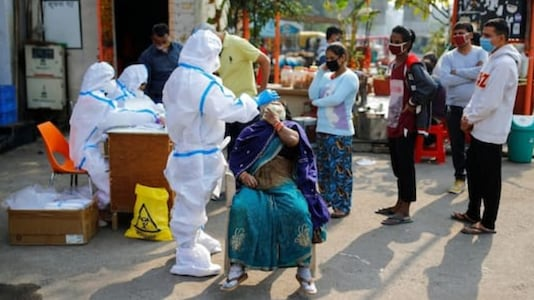A healthcare worker wearing personal protective equipment (PPE) collects a swab sample from a woman amidst the spread of the coronavirus disease (COVID-19), at Delhi-Uttar Pradesh border, in Noida, India, November 19, 2020. REUTERS/Adnan Abidi