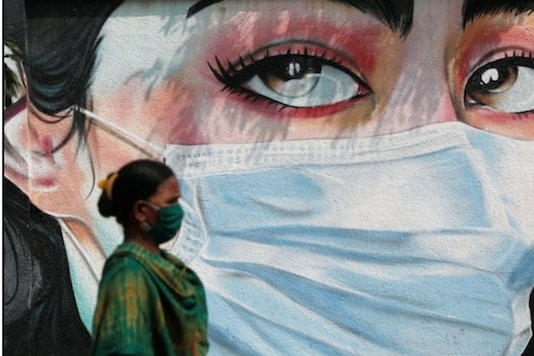 A woman walks past a graffiti of a girl wearing a protective mask amidst the spread of the coronavirus disease (COVID-19).
