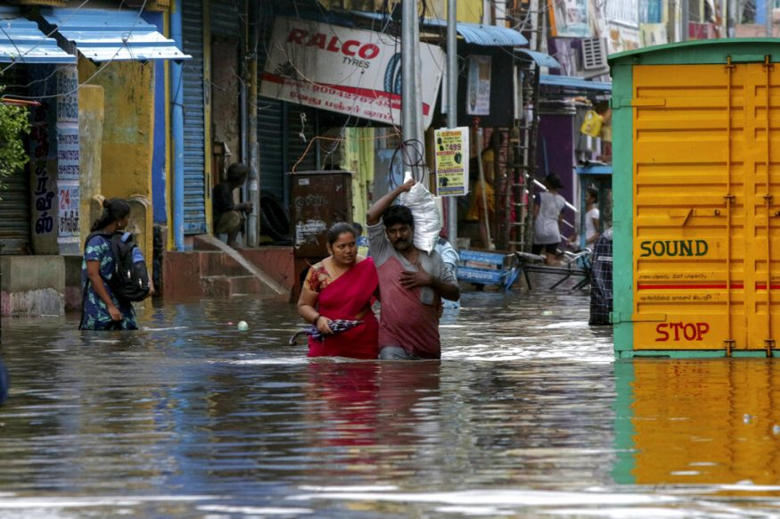 People wade through a flooded street in Chennai. (Image: AP)