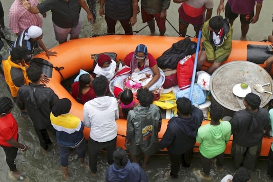 Rescuers help transport a one-month old baby stranded in floodwaters on the outskirts of Chennai. (AP)