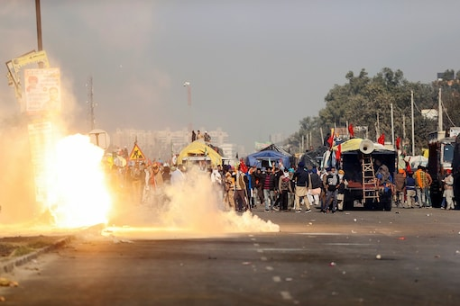 Flames emerge from tear gas released by the Delhi police at Singhu border to stop farmers opposing the newly passed farm bills from entering the national capital. (Reuters)