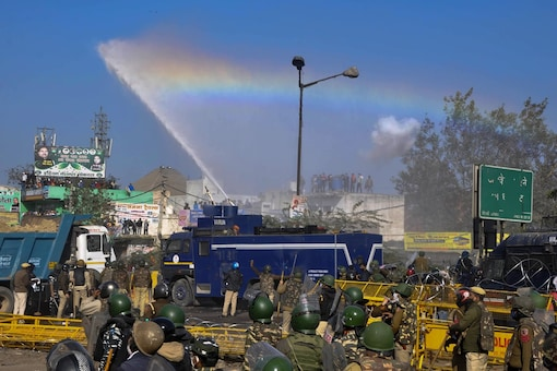 Sonepat: A water cannon spray appears as a rainbow as police personnel try to disperse farmers heading towards Delhi during their 'Delhi Chalo' protest march against the new farm laws, at Kundli border in Sonepat, Friday, Nov. 27, 2020. (PTI)