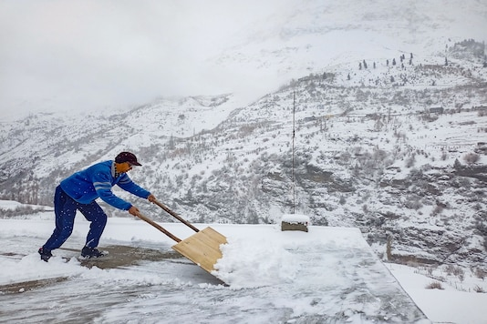 A man clears snow from a roof after fresh snowfall, in Lahaul-Spiti. (PTI)