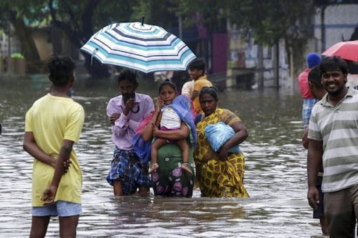 People wade through a flooded street in Chennai. (AP)