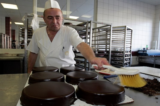 File photo of a confectioner of Hotel Sacher brusheing Sachertorte in a cake factory in Vienna. (For representation/File photo REUTERS)