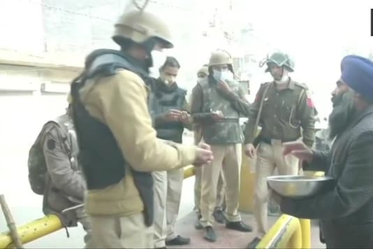 Protesting farmers offer 'prasad' to security personnel as they demonstrate against farm laws.